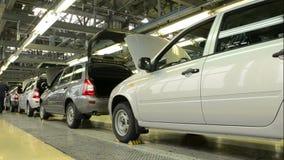De mensen werken bij assemblage van auto's Lada Kalina aan transportband van fabriek AutoVAZ stock video