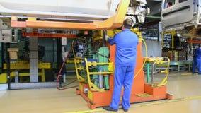 De mensen werken bij assemblage van auto's LADA Largus aan transportband van fabriek AutoVAZ stock videobeelden