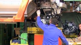 De mensen werken bij assemblage van auto's LADA Largus aan transportband van fabriek AutoVAZ stock video
