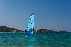 De mensen is wind surfend op het blauwe overzees van Corsica Blauwe windbranding in voorgrond, de aard van Corsica op achtergrond royalty-vrije stock foto's