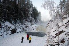 De mensen worden gefotografeerd op de achtergrondwaterval Kivach in bewolkte Januari-dag Karelië, Rusland Stock Fotografie