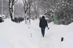 De mensen zijn walkin op de straat na tijdens massieve sneeuwval Stock Foto