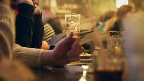 De mensen zitten in de avond in het de bar en het drinken bier stock videobeelden