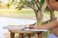 De mensen zitten en gebruiken pennen op notitieboekjes stock foto