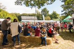 De mensen zitten het eten op hooi bij het Voedselfestival in St Fagans royalty-vrije stock foto's