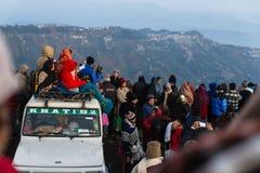 De mensen zitten op de auto met menigte voor het zien van het eerste licht van nieuwe jaar` s dag bij dageraad met bergdorpen Stock Afbeelding
