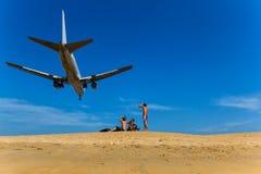 De mensen zitten op het strand en bekijken hen op een vliegtuig die over vliegen Royalty-vrije Stock Foto