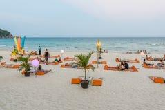 De mensen zitten op tapijten bij het strand van de volle maanpartij Stock Fotografie