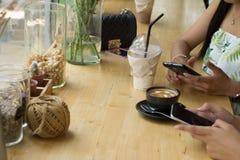 De mensen zitten op de de telefoon en het drinken koffie op een houten lijst in een restaurant stock afbeeldingen