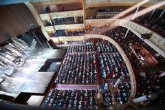 De mensen zitten in theater verwachtend operette Stock Fotografie