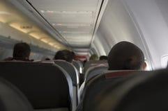 De mensen zitten in de vliegtuigencabine en het wachten op vertrek stock afbeeldingen
