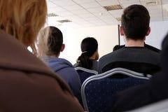 De mensen zitten in de zaal en luisteren aan een lezing Bedrijfs concept royalty-vrije stock afbeelding
