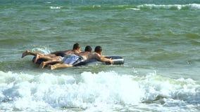 De mensen zwemmen in het overzees op een opblaasbare matras Zij lachen De matrasworpen op de golven stock video