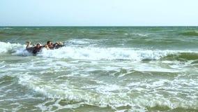 De mensen zwemmen in het overzees op een opblaasbare matras Zij lachen De matrasworpen op de golven Langzame Motie stock video