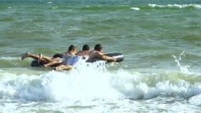 De mensen zwemmen in het overzees op een opblaasbare matras Zij lachen De matrasworpen op de golven Langzame Motie stock footage