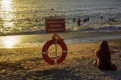 De mensen zwemmen in zonsondergang overzees recht bij het verbiedende teken stock afbeelding