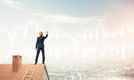 De mensenarchitect trekt silhouet van moderne stad op blauwe hemel gemengd Royalty-vrije Stock Afbeeldingen