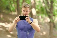 De mensenatleet concentreerde gezicht neemt de aardachtergrond van de smartphonefoto Sportman opleidingspedometer en hoofdtelefoo royalty-vrije stock afbeelding