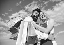 De mensenbaard en het blondemeisje genieten van kopen kleding Het winkelen brengt positieve emoties De familie kocht uitstekende  royalty-vrije stock afbeeldingen
