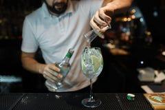 De mensenbarman maakt een heerlijke cocktail met de toevoeging van witte wijn, ijsblokjes en appelplakken op een donkere achtergr royalty-vrije stock fotografie