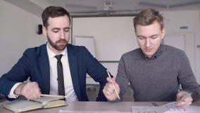 De mensenberoeps werken aan blauwdruk bij lijst in modern bureau stock video