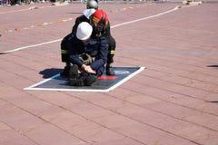 De mensenbrandbestrijder in vuurvaste kostuum en helm spaart sleept trekt de arbeidersmens uit gevaar stock afbeeldingen