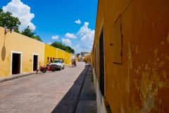 De mensencycli is met drie wielen in een gele straat royalty-vrije stock foto's