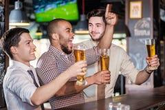 De mensenfans die en op voetbal op TV gillen letten en drinken bier T Stock Afbeelding