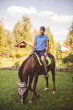 De mensengangen op horseback Concept: hobby, Hobbys, aard, dieren Het paard kauwt het gras Royalty-vrije Stock Foto's
