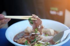 De mensenhand gebruikt eetstokjes aan bestelwagenvarkensvlees in Thaise noedelskom op de lijst royalty-vrije stock afbeelding