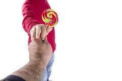 De mensenhand geeft suikergoed aan kind stock afbeeldingen