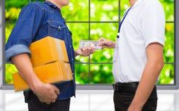 De mensenhand houdt Amerikaans dollargeld en betaalt voor het pakket ord Stock Foto