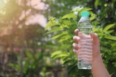 De mensenhand houdt een fles drinkwater royalty-vrije stock foto
