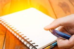 De mensenhand houdt een pen op het notitieboekje Stock Foto's