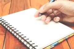 De mensenhand houdt een pen schrijvend op het notitieboekje Royalty-vrije Stock Afbeeldingen