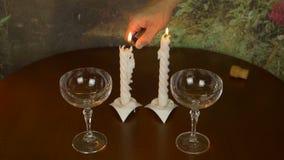 De mensenhand zet aansteker en brandkaarsen op de lijst aan Lege wijnglas twee status Romantische voordien nachten vier stock footage