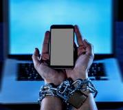 De mensenhanden bonden aan mobiele telefoon met kettingshangslot in Internet of sociale media verslaving royalty-vrije stock foto's
