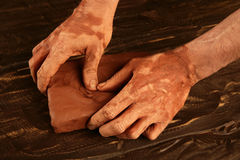 De mensenhanden die van de kunstenaar rode klei voor handcraft werken Stock Afbeelding