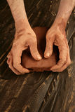 De mensenhanden die van de kunstenaar rode klei voor handcraft werken Stock Foto