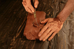 De mensenhanden die van de kunstenaar rode klei voor handcraft werken Royalty-vrije Stock Afbeeldingen