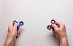 De mensenhanden met populair friemelen spinnerstuk speelgoed op een grijze achtergrond met ruimte voor tekst Stock Fotografie