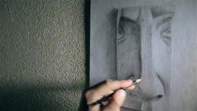 De mensenkunstenaar trekt een neus met een grafietpotlood stock videobeelden