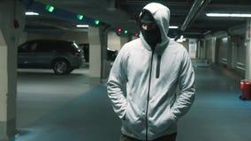 De mensenmisdadiger in zwarte balaclava en kap loopt menacingly en kijkt rond Langzame mo stock videobeelden