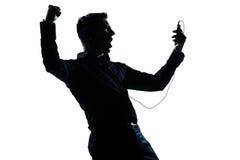 De mensenportret van het silhouet het gelukkige luisteren aan muziek Stock Afbeelding