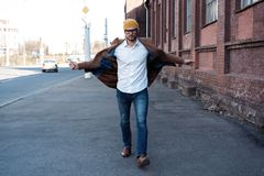 De mensenportret van de manier Jonge mens in glazen die laag dragen die onderaan de straat lopen stock fotografie