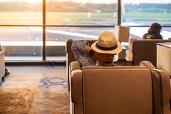 De mensenreiziger die met hoed aan vliegtuig in de ochtendzonsopgang kijken, Aziatische passagierszitting en ontspant in moderne  royalty-vrije stock afbeeldingen
