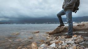 De mensenreiziger met een rugzak bevindt zich op de kust tegen een achtergrond van wolken en een bergketenconcept wandeling Royalty-vrije Stock Foto's