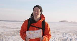 De mensenreiziger met kaart in handen richt de route op een sneeuw behandeld gebied in bergen stock videobeelden