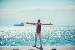 De mensenreiziger met rugzakgreep rised handen op zee water reis en zwerflustconcept de zomervakantie en avonturen stock afbeeldingen
