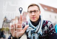 De mensenreiziger richt een vinger op de kaart Mening door het telefoonscherm Stock Afbeelding